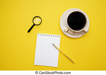 pen Notepad magnifier and coffee Cup on yellow background with copy space top view
