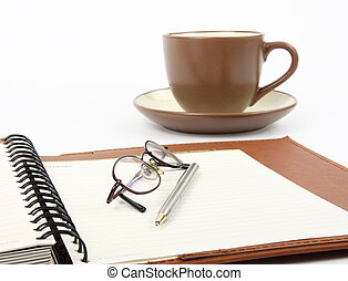 Pen on a spiral notebook with cup of coffee and glasses