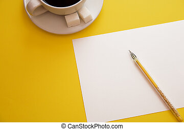 pen white paper and coffee Cup on yellow background with copy space top view
