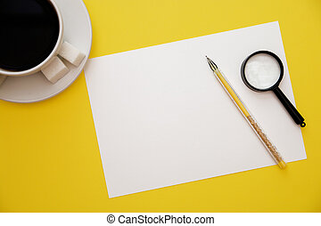 pen white paper magnifier and coffee Cup on yellow background with copy space top view