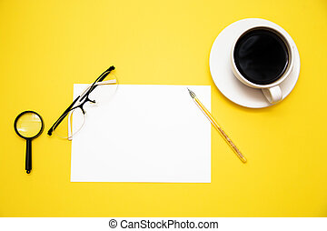 pen white paper magnifier glasses and coffee Cup on yellow background with copy space top view