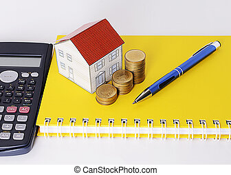 pen with coins stack and paper house on yellow book and calculator