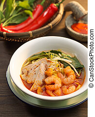 Penang Prawn Mee soup with pork, vegetables, red chili and shrimp in white bowl