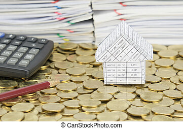 Pencil and calculator with house on stack of gold coins