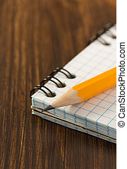 pencil and checked notebook on wood