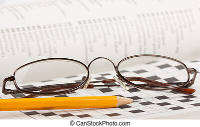 A close-up of a pencil and glasses on a crossword puzzle
