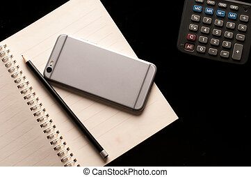 Pencil and mobile phone on Notebook with calculator use in business office black background