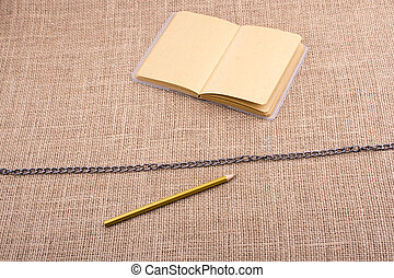 Pencil and notebook with a chain in the middle