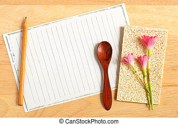 Pencil and spoon with paper on wooden background