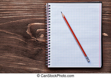 Pencil and squared notepad on pine brown wooden board office con