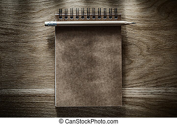 Pencil brown notepad on wooden board