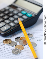 Pencil, calculator and coins