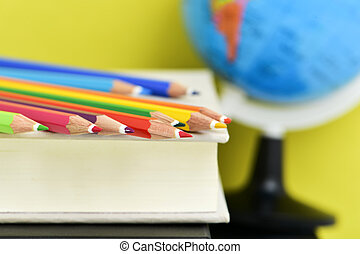 pencil crayons, books and terrestrial globe - closeup of a...
