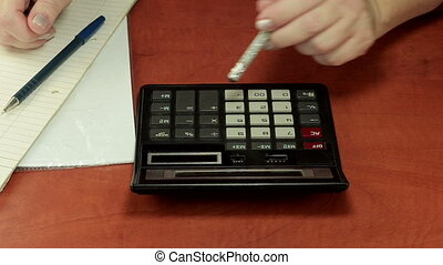 Woman left hand is pushing calculator buttons with pencil eraser and ready to record outcome by right hand