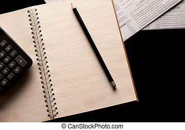 Pencil on Notebook with calculator use in business office black background