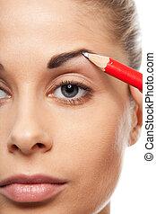 Pencil woman's eyebrows with a carpenters pen - Pencil...