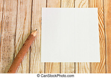 Pencil wood bark with paper note on wooden background