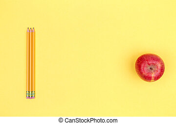 Pencils and apple on a yellow background. Back to school concept