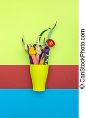 Pencils in a cover of fulled wool in a green cup on a colored background