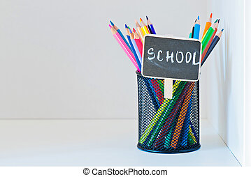 Pencils in a holder on the light-coloured shelf with...
