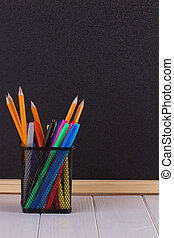 Pencils in the stand in front of black school Board