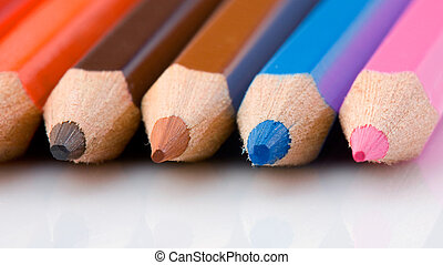 Pencils of many colors aligned with reflection on floor