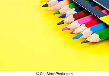 Coloured pencils in box on yellow background with place for text.