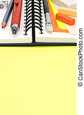 pencils, paintbrush, colorful pieces of chalk with sketchbook on yellow desk