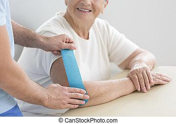 pendant, femme aînée, thérapie, kinesiotaping