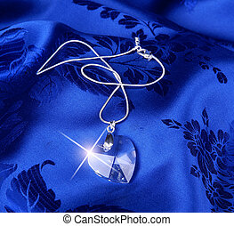 Pendant - Heart pendant and silver chain on blue fabric