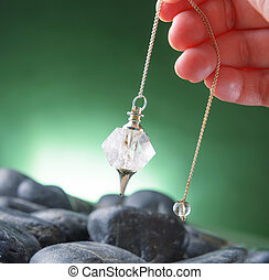 Pendulum - Hand with pendulum, tool for dowsing.