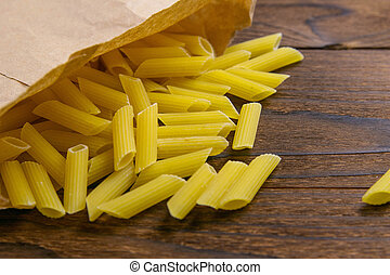 Pene Lisce pasta in a craft paper bag on a wooden table