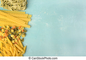 Penne, Mafalde, Tagliatelle, Spaghetti laid out on a blue background. Beautiful composition of pasta with space for text, copy space.