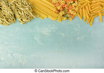 Penne, Mafalde, Tagliatelle, Spaghetti laid out on top of a blue background. Beautiful composition of pasta with space for text, copy space.