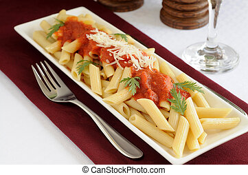 Plate of penne pasta with tomato sauce and fresh herbs.