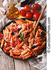 Penne with eggplant and tomatoes closeup and ingredients. Vertical