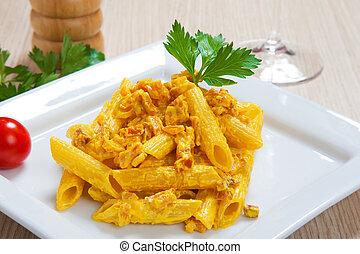 Penne with speck and saffron on a dish