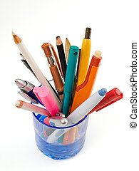 Colourful pens and pencils in a blue glass isolated on a white background