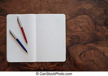 pens on a copy book isolated on wooden background