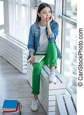 pensamento mulher, jovem, sentando, janela, casaco, calças brim