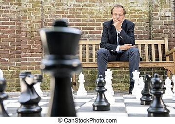 pensamiento, hombre que sienta, en, un, vida, dimensionar, al aire libre, tablero del ajedrez