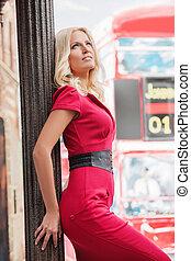 pensativo, beauty., atraente, mulher jovem, em, vermelho, inclinar-se, em, a, coluna, e, olhando