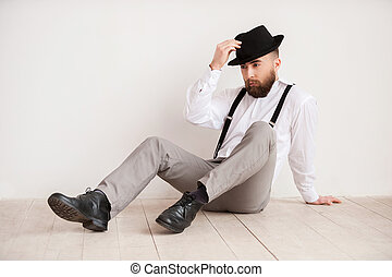 pensativo, chão, afastado, sentando, jovem, mão, olhar, confiante, enquanto, man., segurando, bonito, chapéu, casual, esperto, homem