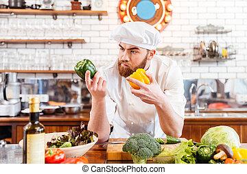 pensativo, chef, cocinero, escoger, vegetales, para, ensalada, en, el, cocina