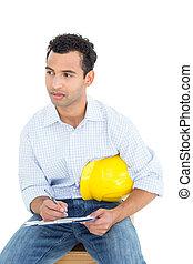 pensativo, factótum, con, sombrero duro amarillo, escritura, en, portapapeles