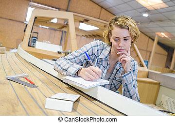pensativo, hembra, trabajador industrial, trabajando, con, tablas de madera
