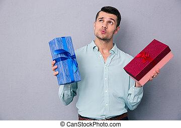 pensativo, homem jovem, segurando, dois, caixa presente