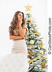 pensativo, mujer joven, posición, delante de, árbol de navidad