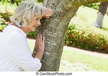 pensativo, mujer mayor, propensión, a, árbol, en, parque