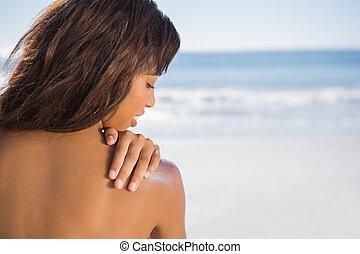 pensativo, mulher, aplicando, creme sol, ligado, dela, ombro